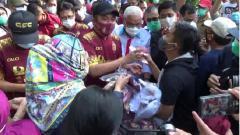 Indosport - Gubernur Sumsel, Herman Deru, menerima uang pembayaran dari pembeli jersey Sriwijaya FC di Kambang Iwak, Palembang.