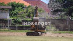 Indosport - Seorang pekerja saat mengoperasikan buldozer untuk mengeruk lapangan di Stadion Ngurah Rai, Denpasar.