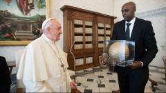 Indosport - Pebasket NBA Anthony Tolliver menyerahkan kenang-kenangan untuk Paus Fransiskus.