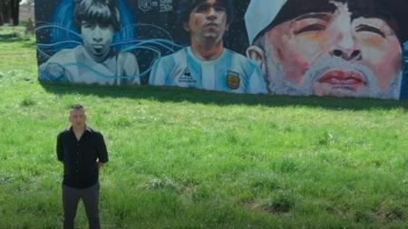 Pelatih sepak bola asal Argentina, Carlos Alberto Gomez, ketika berfoto di depan mural Diego Maradona. - INDOSPORT