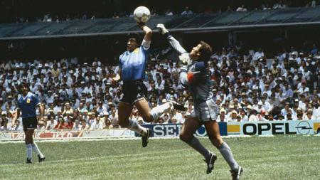 Diego Maradona (tengah), saat mencetak gol menggunakan tangannya ke gawang Inggris yang dijaga Peter Shilton (kanan), pada babak perempat final Piala Dunia 1986. - INDOSPORT