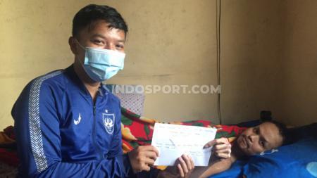 Media Officer PSIS, Alvin Syaptia Pratama ketika menyerahkan bantuan berupa uang tunai dari manajemen PSIS kepada Nanang Fauzi. - INDOSPORT