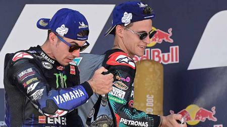 Pembalap asal Spanyol, Maverick Vinales, dan pembalap asal Prancis, Fabio Quartararo, saat merayakan hasil balapan di atas podium. - INDOSPORT