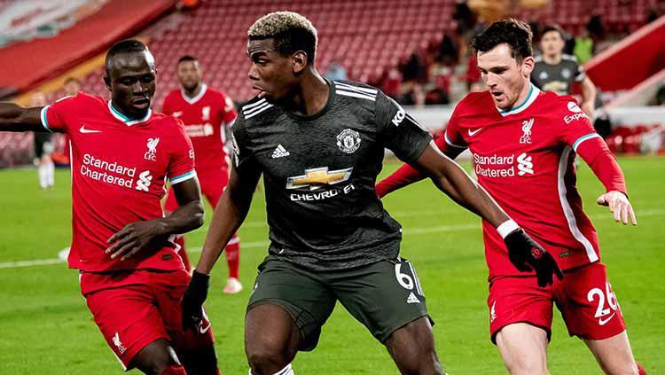 Paul Pogba dari Manchester United bersaing dengan Sadio Mane dan Andrew Robertson dari Liverpool selama pertandingan Liga Premier antara Liverpool dan Manchester United di Anfield pada 17 Januari 2021 di Liverpool, Copyright: Ash Donelon/Manchester United via Getty Images