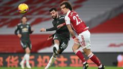 Indosport - Bruno Fernandes melepaskan tembakan yang coba dihalau David Luiz di laga Arsenal vs Manchester United