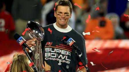 Tom Brady memegang trofi juara Superbowl. - INDOSPORT