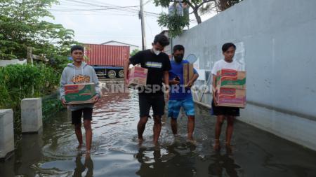 Pemain PSIS Hari Nur Yulianto (kaos hitam) saat mengantarkan bantuan bagi korban banjir. - INDOSPORT