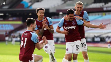 Pemain West Ham United, Jesse Lingard merayakan dengan rekan setimnya Declan Rice, Pablo Fornals dan Tomas Soucek usai mencetak gol kedua pada pertandingan Liga Premier antara West Ham United vs Tottenham Hotspur di London, Inggris, Senin (21/02/2021). - INDOSPORT