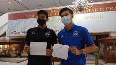 Indosport - Dua pemain PSIS Semarang, Septian David dan Alfeandra Dewangga saat menunjukkan surat sudah divaksin tahap pertama.