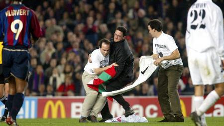 Penyusup lapangan ditangkap petugas dalam pertandingan LaLiga Spanyol antara Barcelona kontra Real Madrid, 16 Maret 2002. - INDOSPORT