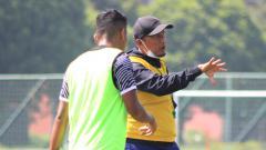 Indosport - Pelatih Madura United, Rahmad Darmawan, memberikan arahan kepada pemainnya saat latihan di lapangan Batununggal, Kota Bandung, Sabtu (20/3/21).