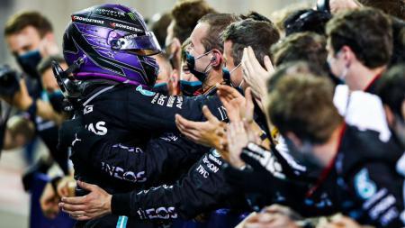 Pembalap Mercedes asal Inggris, Lewis Hamilton, merayakan bersama tim setelah memenangi balpan GP Bahrain di Bahrain International Circuit, Sakhir, Minggu (28/3/2021). - INDOSPORT