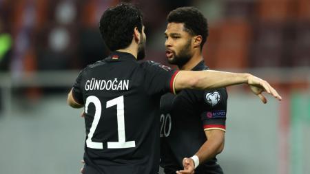 Pemain Jerman, Serge Gnabry (kanan), merayakan golnya bersama Ilkay Gundogan saat melawan Rumania pada laga kualifikasi Piala Dunia di National Arena, Bucharest, Rumania, Minggu (28/3/2021). - INDOSPORT