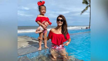 Farah Quinn tampil manis dengan baju renang merah saat berenang bersama sang putri. - INDOSPORT