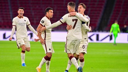 Skuad AS Roma merayakan gol ke gawang Ajax Amsterdam dalam laga leg pertama perempatfinal Liga Europa, Jumat (09/04/21) dini hari WIB. - INDOSPORT