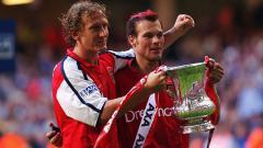 Indosport - Pose Ray Parlour dan Freddie Ljungberg memegang trofi Piala FA usai mengalahkan Chelsea di final, 4 Mei 2002.