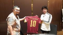 Indosport - Presiden Sriwijaya FC, Hendri Zainuddin, memberikan jersey kepada Atta Halilintar.
