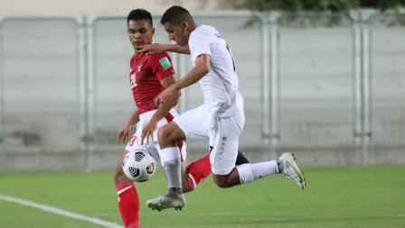 Bek Timnas Indonesia, Rachmat Irianto (kiri) membayangi pergerakan pemain Afghanistan pada laga uji coba di Iranian Club Stadium, Dubai, Uni Emirat Arab (UEA), Selasa (25/05/21).