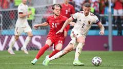 Indosport - Toby Alderweireld dari Belgia membawa bola sambil dibayangi oleh pemain Denmark, Mathias Jensen, pada laga Grup B Euro 2020, Jumat (17/06/21) dini hari WIB.