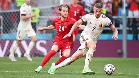 Toby Alderweireld dari Belgia membawa bola sambil dibayangi oleh pemain Denmark, Mathias Jensen, pada laga Grup B Euro 2020, Jumat (17/06/21) dini hari WIB.