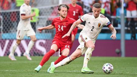 Toby Alderweireld dari Belgia membawa bola sambil dibayangi oleh pemain Denmark, Mathias Jensen, pada laga Grup B Euro 2020, Jumat (17/06/21) dini hari WIB. - INDOSPORT