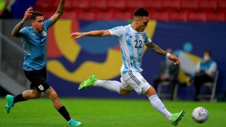 Lautaro Martinez (kanan) berusaha melepaskan tembakan dalam laga Grup B Copa America antara Argentina vs Uruguay, Sabtu (19/06/21) pagi WIB. - INDOSPORT