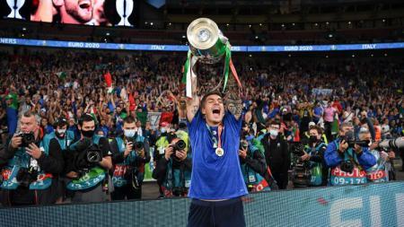 Fullback kanan Italia, Giovanni Di Lorenzo, tengah mengangkat trofi juara Euro 2020. - INDOSPORT