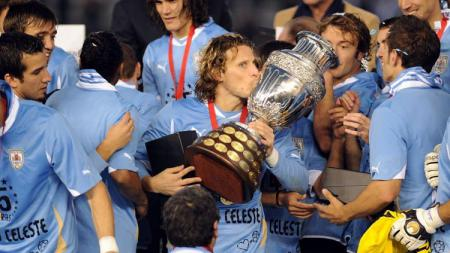 Legenda Uruguay, Diego Forlan, mengangkat trofi Copa America usai mengalahkan Paraguay di final, 24 Juli 2011. - INDOSPORT