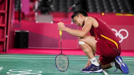 Kento Momota tertunduk setelah tersingkir dari Olimpiade 2020 usai dikalahkan wakil Korea Selatan, Heo Kwang-hee, dua set langsung, Rabu (28/07/21) malam WIB. - INDOSPORT
