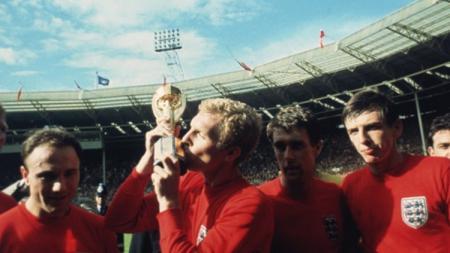 Kapten Inggris, Bobby Moore, mencium trofi Piala Dunia usai mengalahkan Jerman Barat di final, 30 Juli 1966. - INDOSPORT