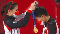 Indosport - Peraih medali emas Greysia Polii dari Indonesia menempatkan medali pada rekan setimnya Apriyani Rahayu di Olimpiade Tokyo 2020.