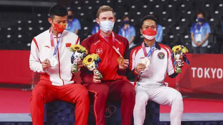 Peraih medali emas Viktor Axelsen asal Denmark berpose dengan Chen Long (China) dan Anthony Ginting (Indonesia) di Olimpiade Tokyo 2020. - INDOSPORT
