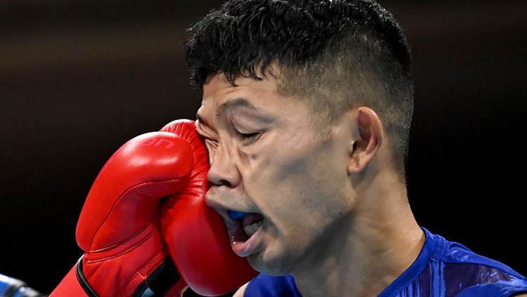 Ryomei Tanaka (Jepang, seragam biru) menerima pukulan hook kiri Yuberjen Rivas (Kolombia) di perempat final tinju 48-52 kg Olimpiade Tokyo 2020. Copyright: Luis Robayo - Pool/Getty Images
