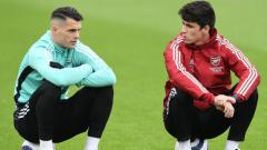 Indosport - Carlos Cuesta (kanan) kala mengobrol dengan Granit Xhaka.