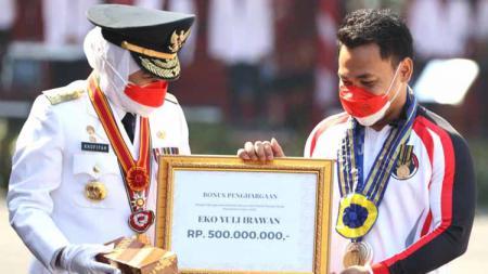 Gubernur Jawa Timur Khofifah Indar Parawansa memberikan lencana Jer Basuki Mawa Beya ke Eko Yuli Irawan di Gedung Negara Grahadi. Selasa (17/08/21). - INDOSPORT