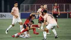 Indosport - Pergerakan gelandang Bali United dihentikan pemain Persik Kediri, Risna Prahalabenta.