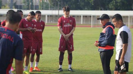 Para penggawa Madura United tengah mendengarkan arahan dari sang pelatih Rahmad Darmawan. - INDOSPORT