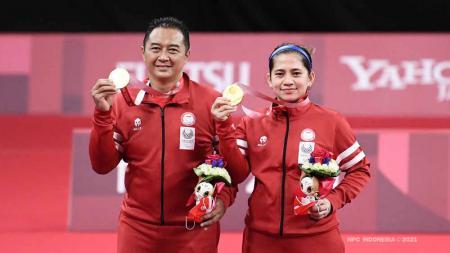 Peraih medali emas Susanto Hary dan Oktila Leani Ratri dari Tim Indonesia berpose di podium untuk Ganda Campuran Paralimpiade Tokyo 2020. - INDOSPORT
