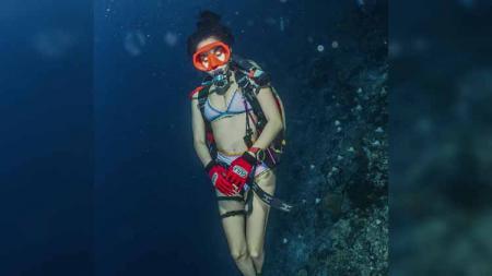 Kian mahir menyelam, aktris Kirana Larasati menikmati perjalanan bawah laut hingga bersembunyi di terumbu karang. - INDOSPORT