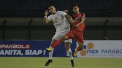 Indosport - Bek kiri PSM Makassar, Abdul Rachman, berduel dengan pemain Persebaya Surabaya