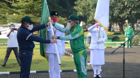 Gubernur Sumut, Edy Rahmayadi (kiri), menyerahkan bendera pataka kepada Ketua kontingen yang juga Ketua KONI Sumut, John Ismadi Lubis (kanan). - INDOSPORT
