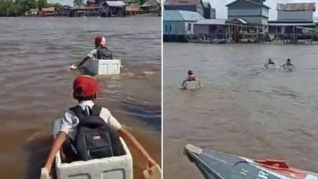 Media sosial dihebohkan video berdurasi 2 menit yang menunjukkan 3 anak SD yang terpaksa menaiki kotak styrofoam untuk menyeberangi sungai demi pulang ke rumah. - INDOSPORT