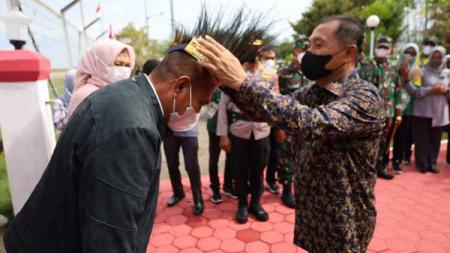 Wakil Bupati Merauke, Riduan, saat menyematkan hiasan kepala kepada Gubernur Sumut, Edy Rahmayadi, saat baru tiba di Merauke. - INDOSPORT