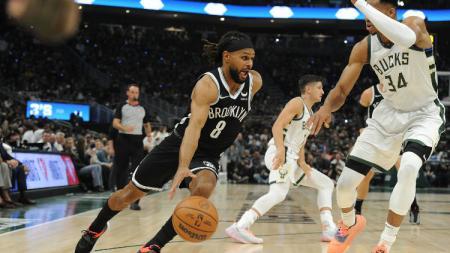 Patty Mills (Nets) mencoba keluar dari hadangan Giannis Antetokounmpo (Bucks) di laga pembuka NBA 2021-2022 (20/10/21). - INDOSPORT