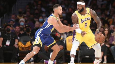 Stephen Curry (Warriors) mencoba merebut bola dari LeBron James (Lakers) di laga kedua NBA (20/10/21). - INDOSPORT