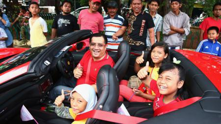 Anggota Ferrari Owners Club Indonesia berfoto bersama anak-anak warga Kelurahan Kebon Bawang, Tanjung Priok, Jakarta Utara, Minggu (18/01/15). - INDOSPORT