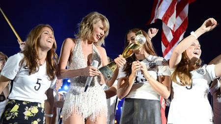 Taylor Swift antusias saat memegang trofi Piala Dunia Wanita. - INDOSPORT