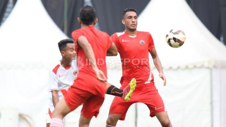Pemain belakang Persija Jakarta, William Pacheco (kanan) berebut bola dengan salah satu official team. Copyright: © Herry Ibrahim/INDOSPORT