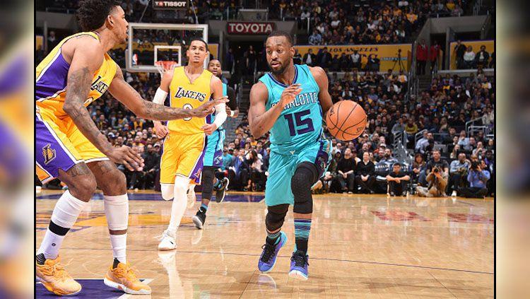 Pemain Charlotte Hornets, Kemba Walker berusaha melewati penjagaan pemain Lakers. Copyright: © Andrew D. Bernstein/NBAE via Getty Images