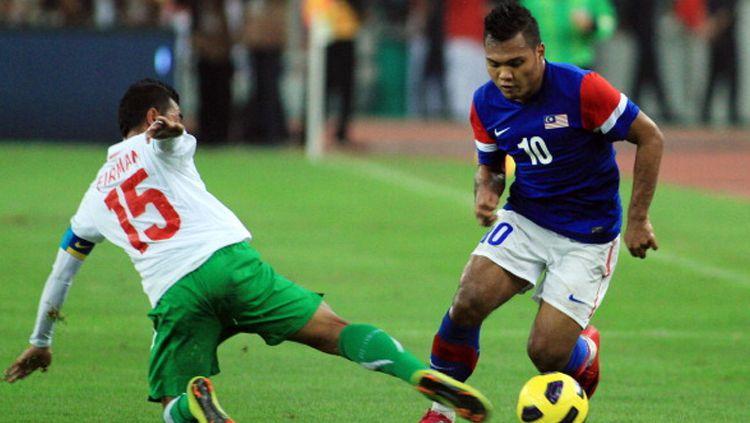 Mantan striker Timnas Malaysia yang pernah berkarier di Liga Indonesia, Safee Sali berusaha melewati hadangan Firman Utina. Copyright: © KAMARUL AKHIR/AFP/Getty Images